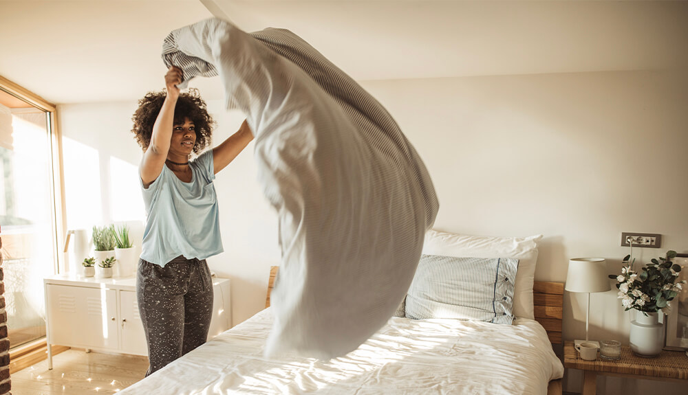 Person shaking out duvet over bed