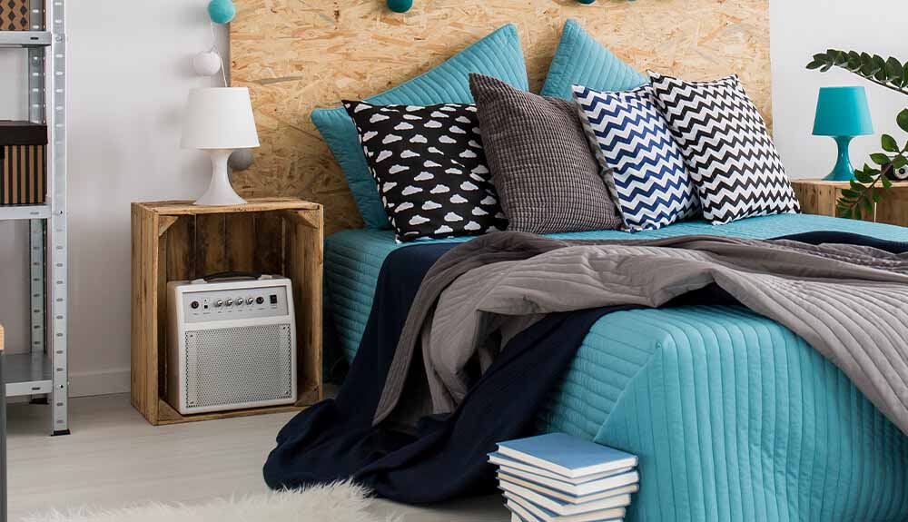 Bed made with bright turquoise blanket and black and white pillows