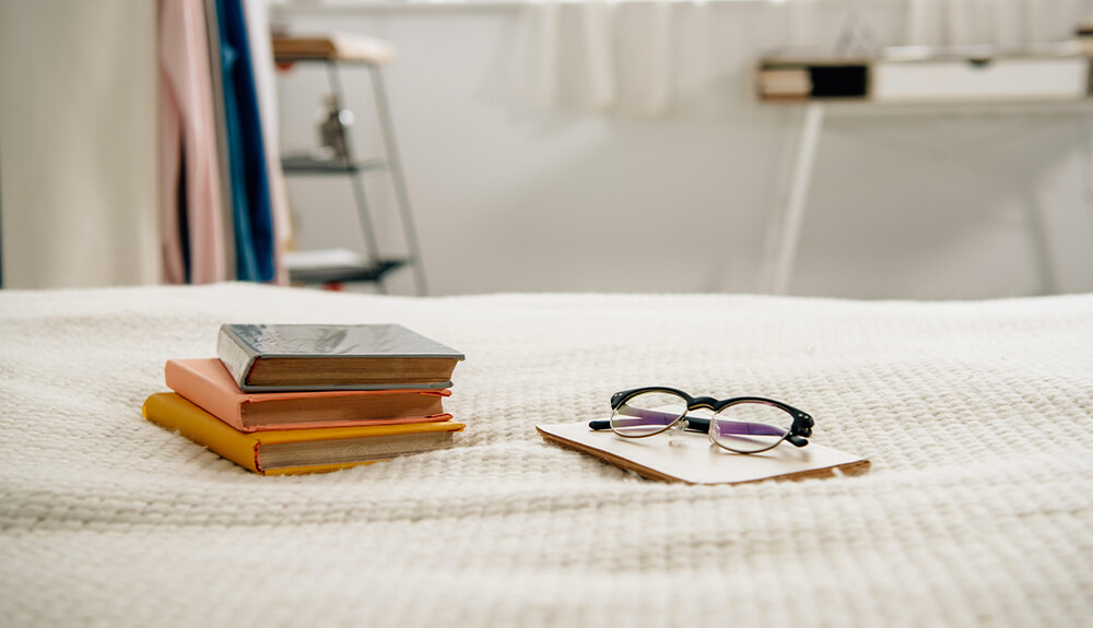 Books and reading glasses laid out on bedspread