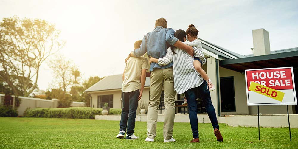 Family of four standing on lawn in front of house with Sold sign