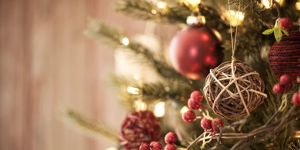 Closeup of Christmas tree branches hung with balls of twine and round red ornaments