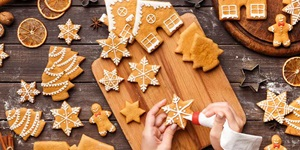 Hands piping icing onto snowflake cookie over background of wooden surface scattered with other festive cookies