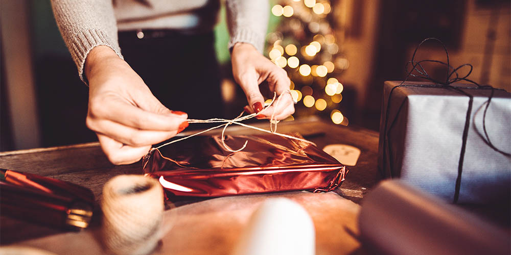 A woman ties a bow on a wrapped gift