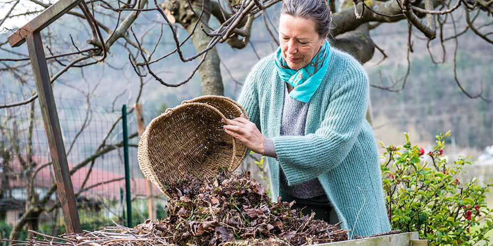 A woman empties a basket of leaves onto a table outdoors