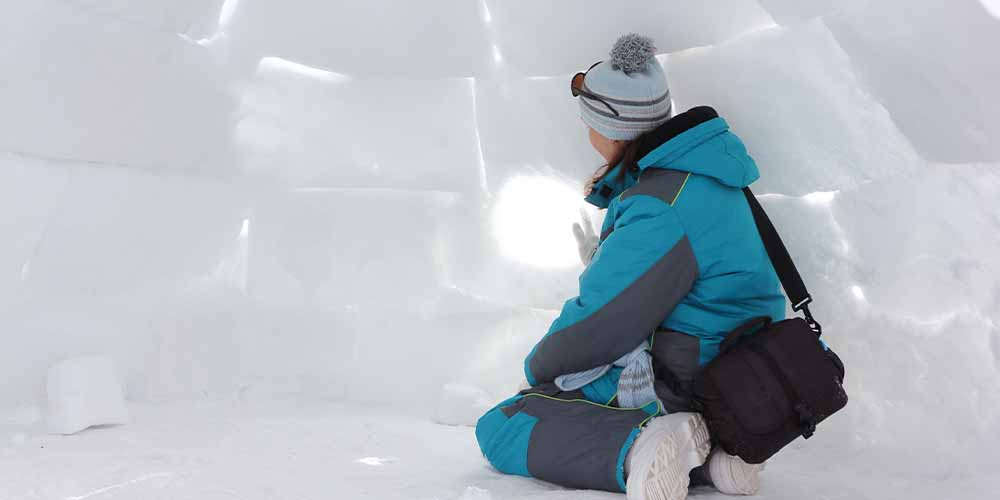 A young person builds an igloo out of snow