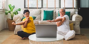 A couple sit on their living room floor stretching their arms in front of a laptop