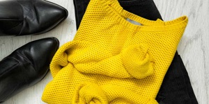 A mustard-coloured sweater is folded on top of black pants, next to a pair of black ankle boots