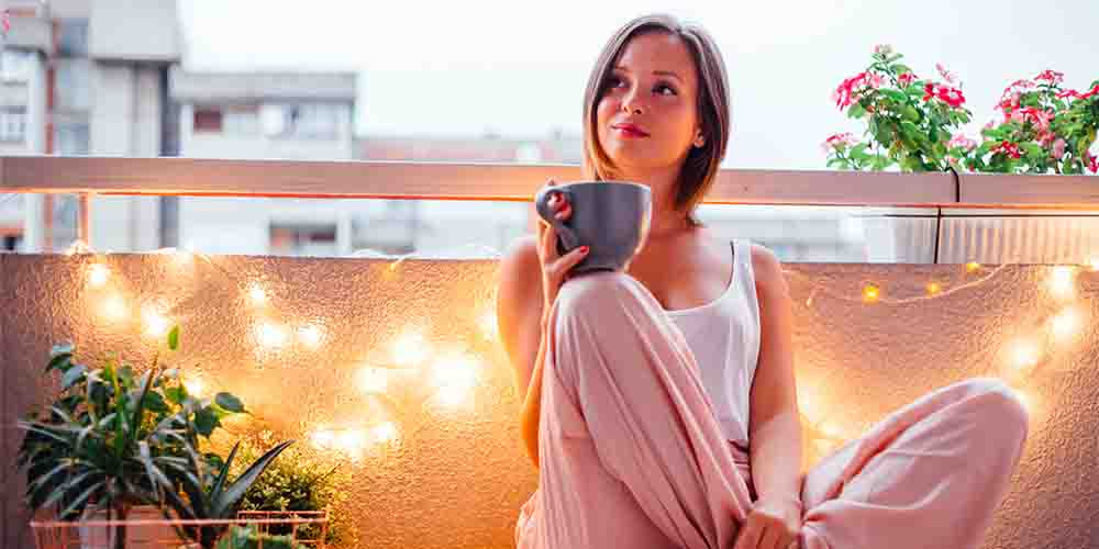 A woman drinks a cup of tea on her balcony