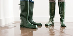 Two people in rubber boots standing in a pool of water