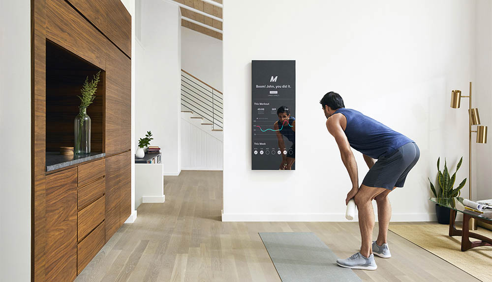 A man stands in front of the Mirror, which displays stats about his workout