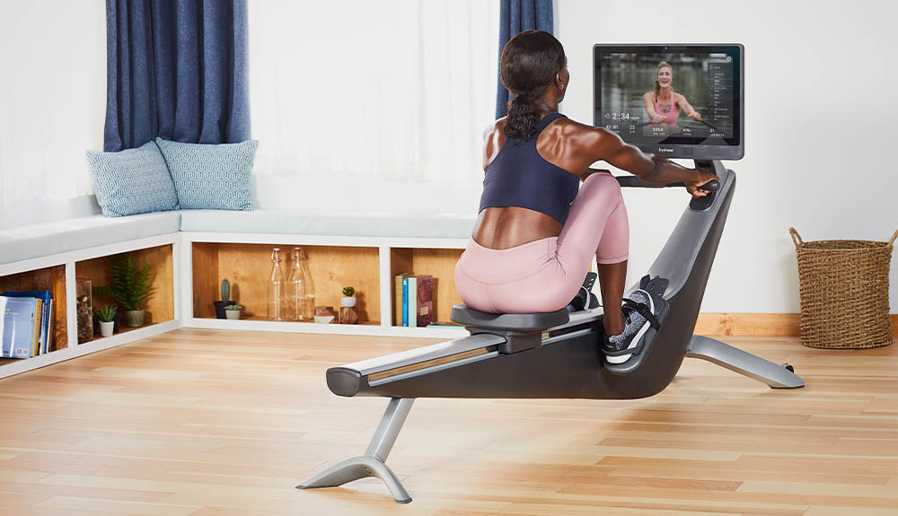 A woman exercises on the Hydrow rowing machine in her home