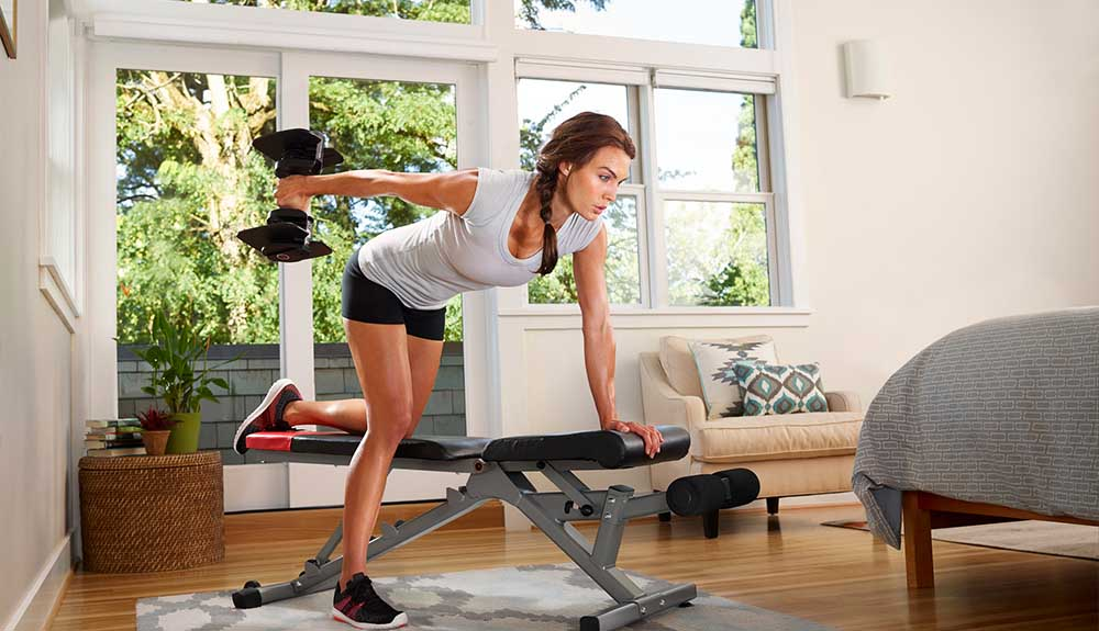 A woman uses the Bowflex SelectTech 560 dumbbells in her home