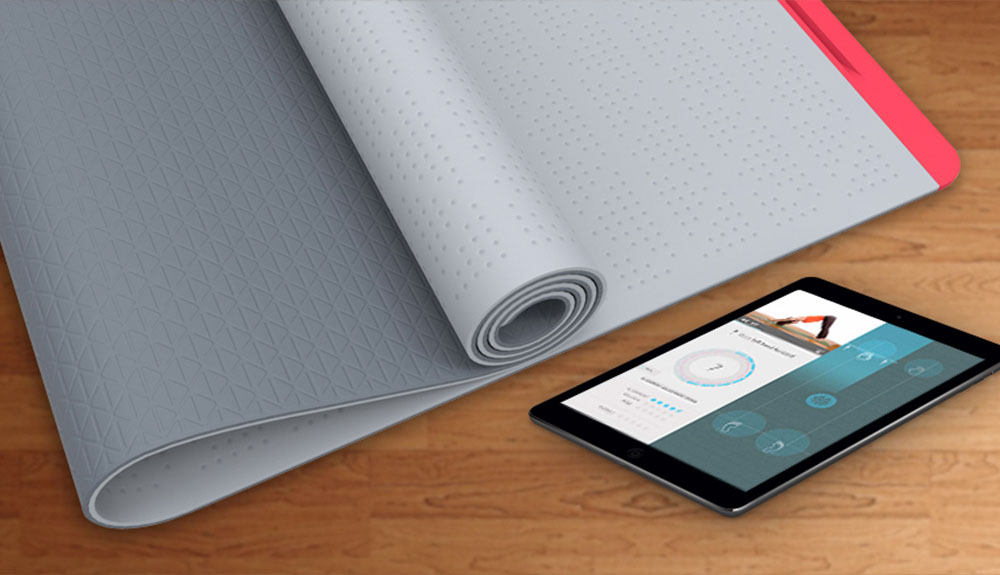 A SmartMat yoga mat is rolled up on the floor next to an iPad