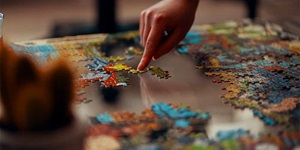 A finger is seen pushing pieces of a puzzle on a table