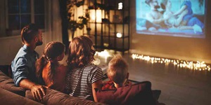A family sits on a couch watching a movie projected onto their living room wall