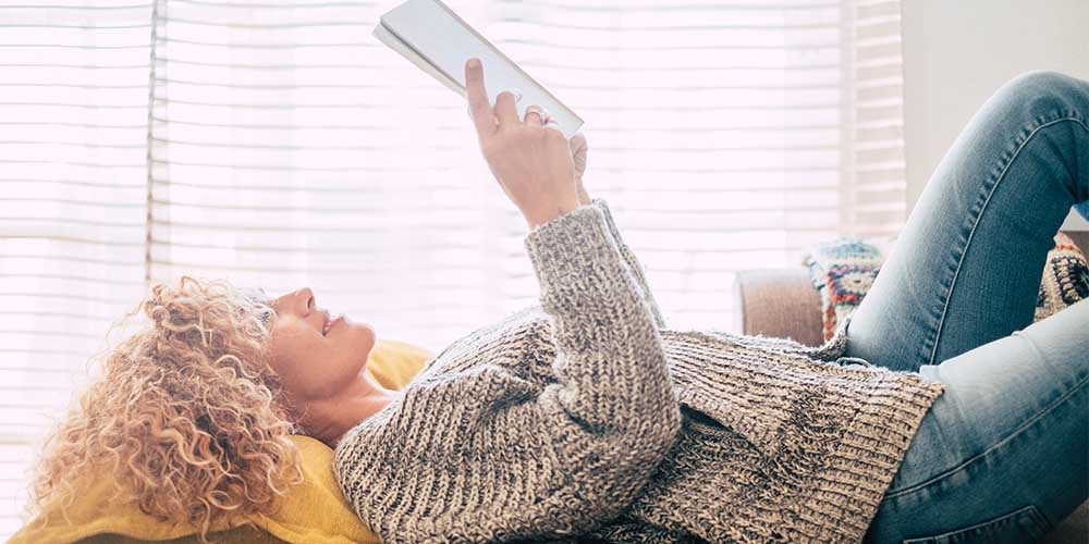 A woman is shown lying down reading a book