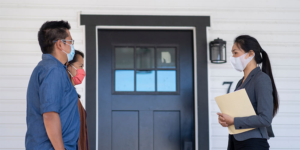 A realtor and two prospective home buyers are shown wearing masks in front of a front door