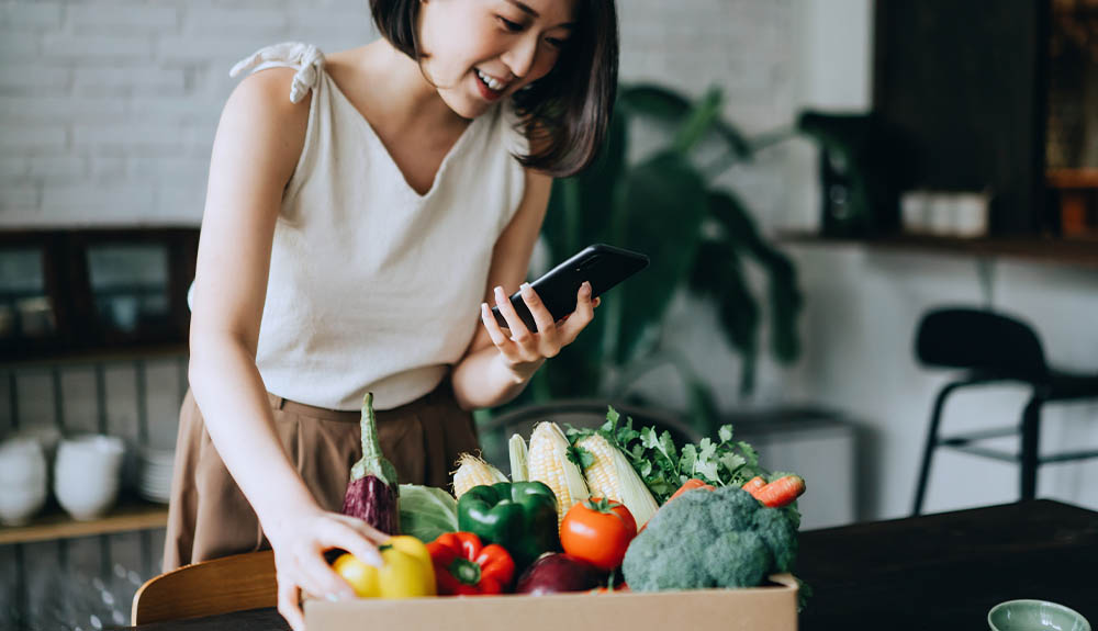 A woman looks at her phone as she unpacks a box of produce in her kitchen