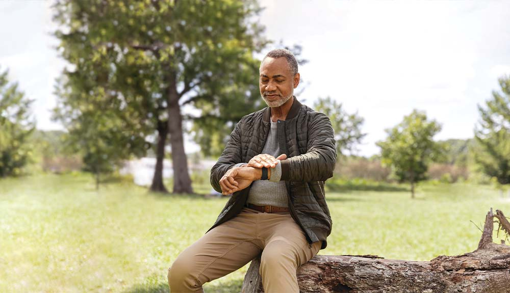 A man sits on a log in a rural setting as he looks at a fitness tracker on his wrist