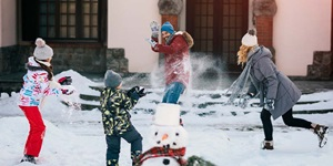 A family has a snowball fight in front of their house with a snowman in the foreground