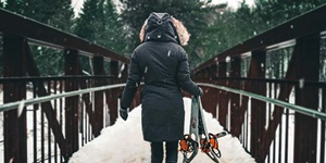 A person is shown from behind, carrying a pair of snowshoes while walking on a pedestrian bridge