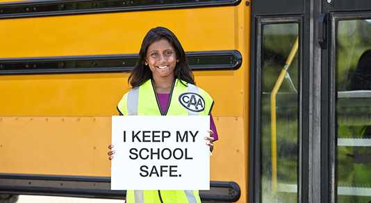 Safety school patroller holding a sign in front of the school bus