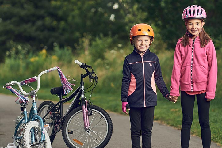 Two kids wearing bike helmets with bikes on the left