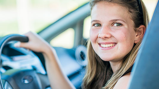 Teenage girl holding the steering wheel with her right hand