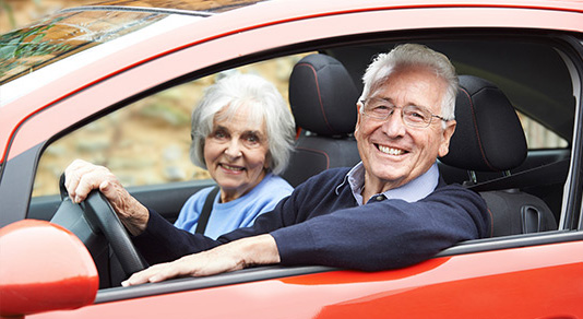 Senior couple driving red car