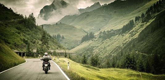 Man riding a motor cycle on a raod between lush green mountains