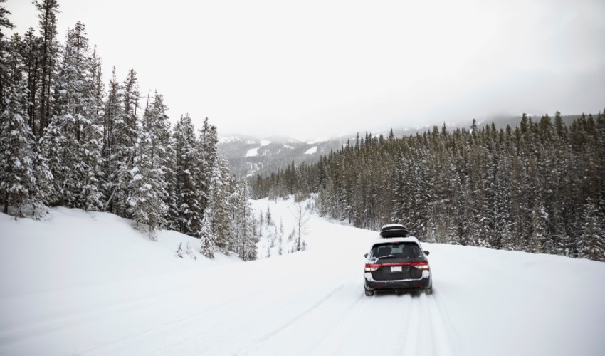 Car driving on snow covered remote road.