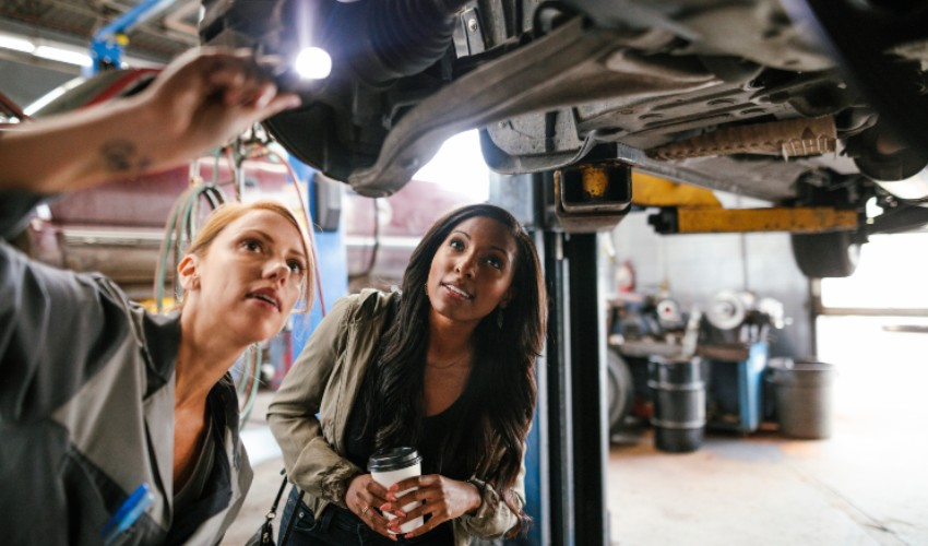 Female mechanic showing a female customer the underbody of a car on a lift in a garage.