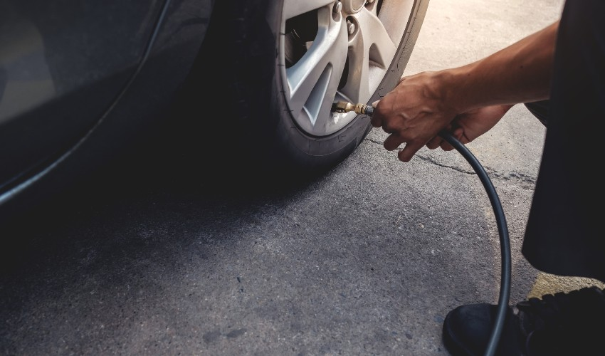 Man filling parked car tire with air.