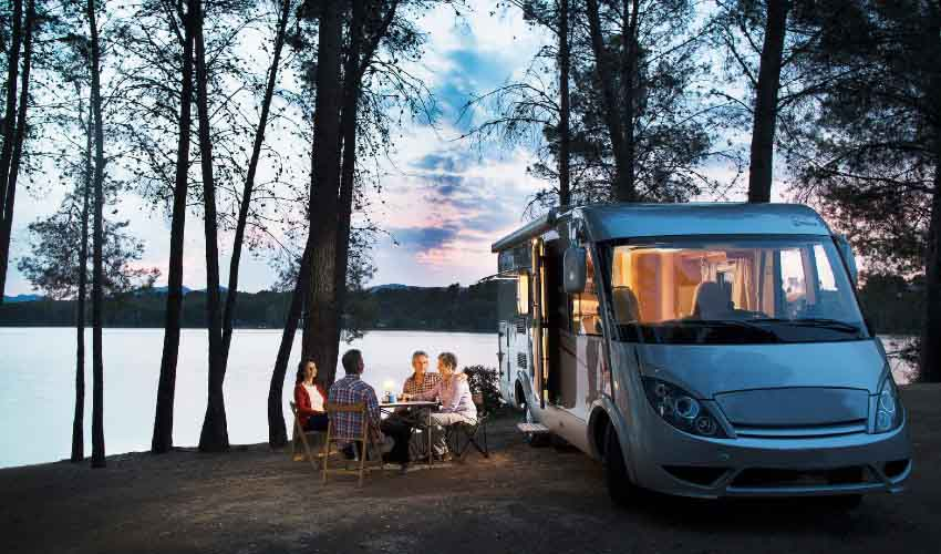Two couples sitting by a lake and a Class B motorhome at dusk.