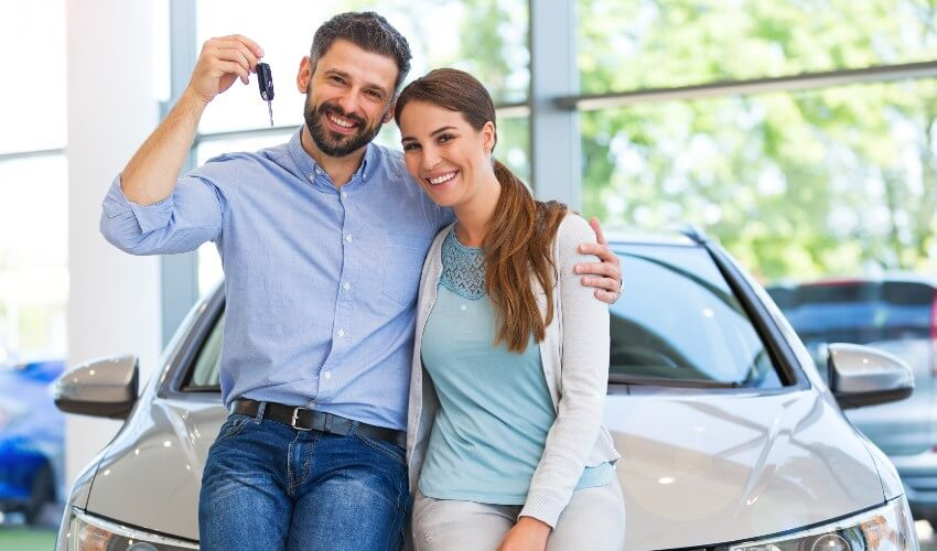 Young happy couple holding up car keys in front of car in car dealership.
