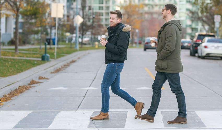 Two men carrying a coffee walking across a crosswalk.