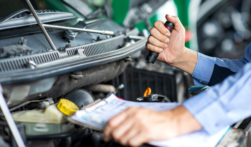 Man with a flashlight and checklist inspecting under the hood of a used car.