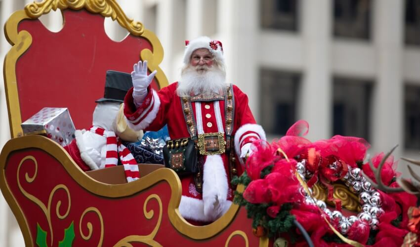Santa Claus on sleigh in parade.