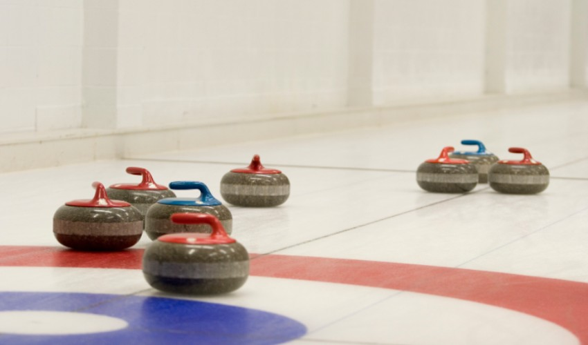 Curling rocks with red and blue handles.