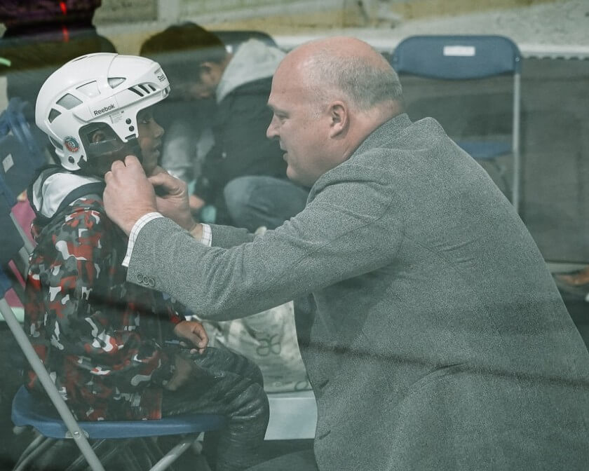 An elderly gentleman helping a young child put on a skating helmet.