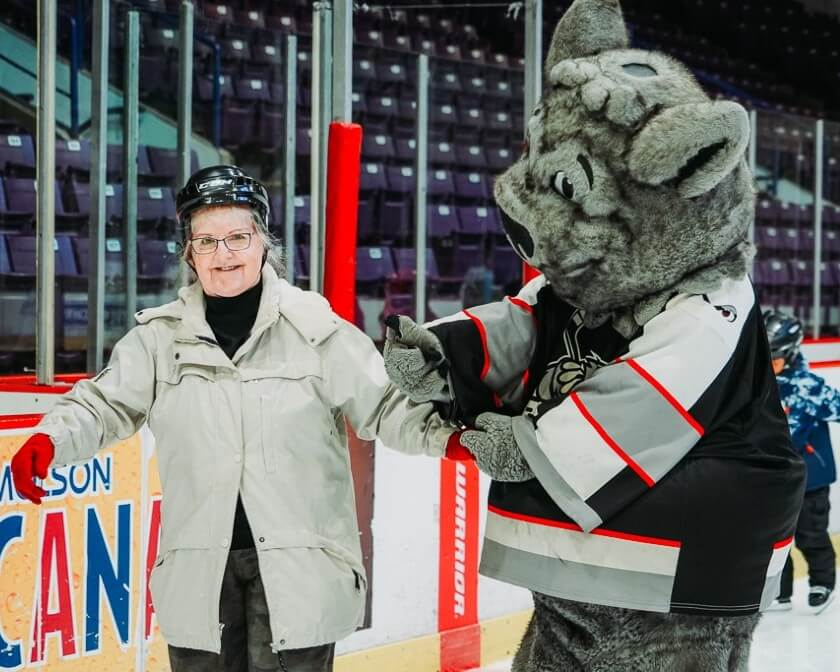 Elderly woman skating with Brampton Beast Mascot Boomer.