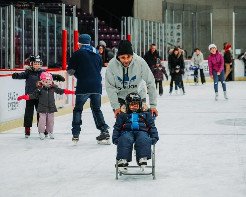 Father skating and pushing a child on a chair at the CAA Centre.