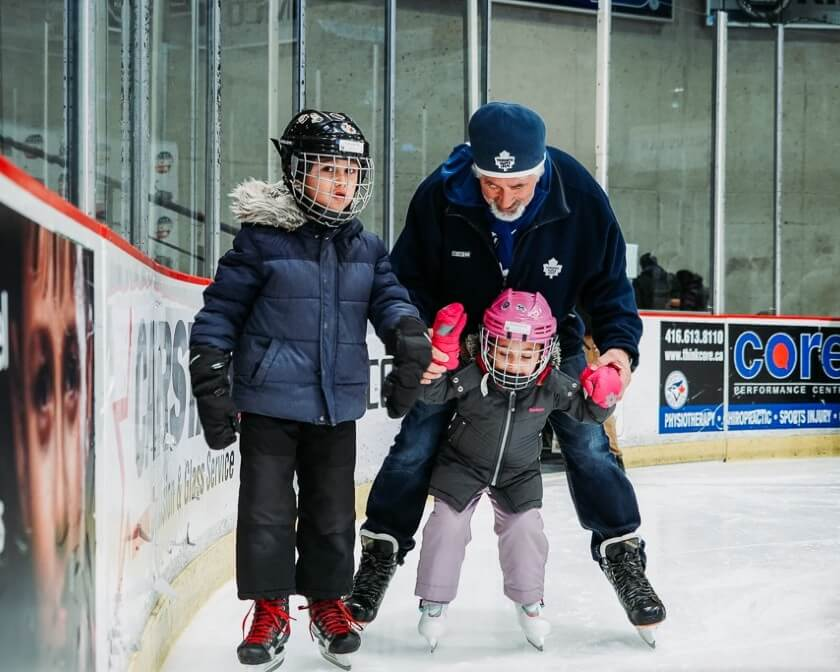 Grandparent skating with two grandchildren at the CAA Centre.