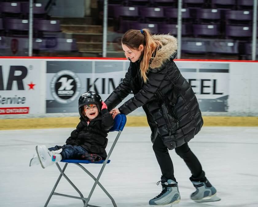 Mother skating with a child on a chair at the CAA Centre.