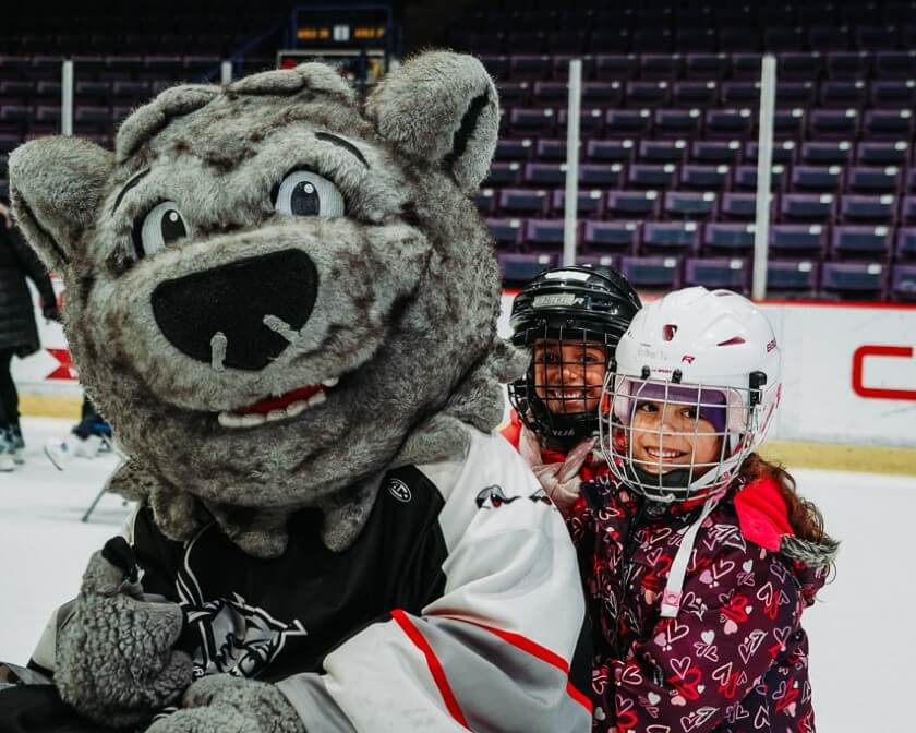 Two happy children with the Brampton Beast mascot Boomer on the ice at the CAA Centre.