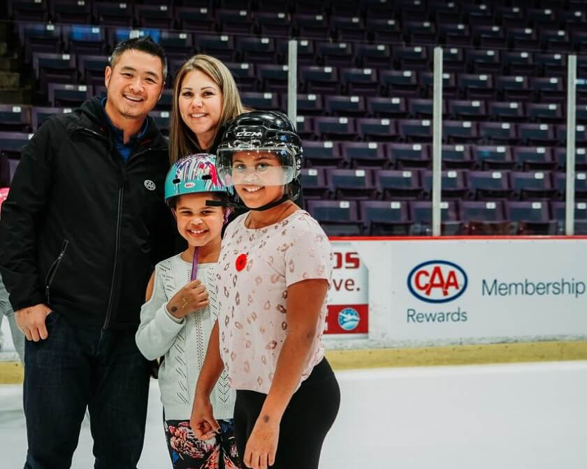 Two parents skating with two young children during a CAA family skate event in Brampton.