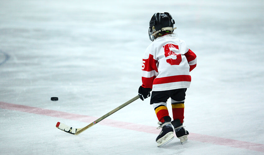 Rear view of a young boy playing ice hockey.