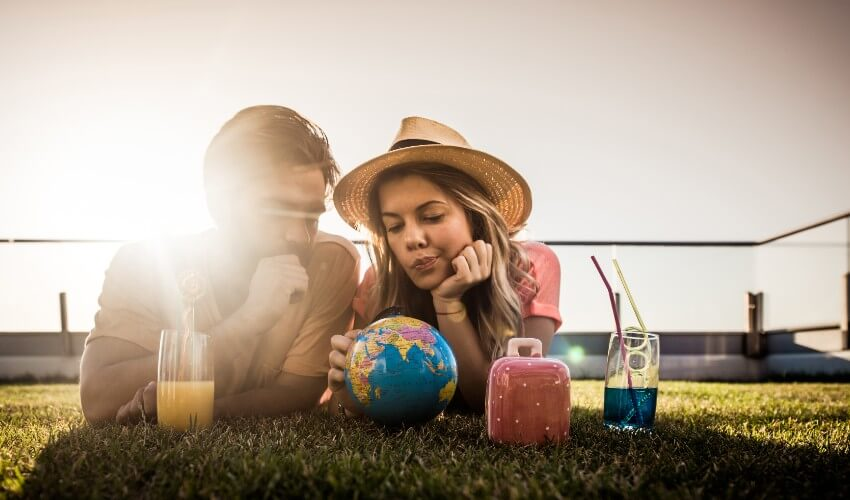 Young couple lying on the grass looking at a small world globe.
