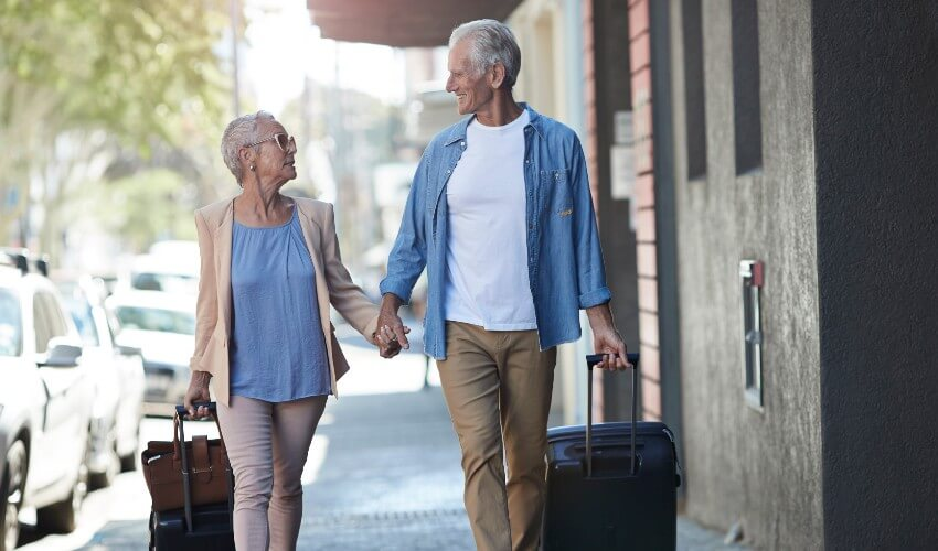 Mature couple walking on city street with suitcases.