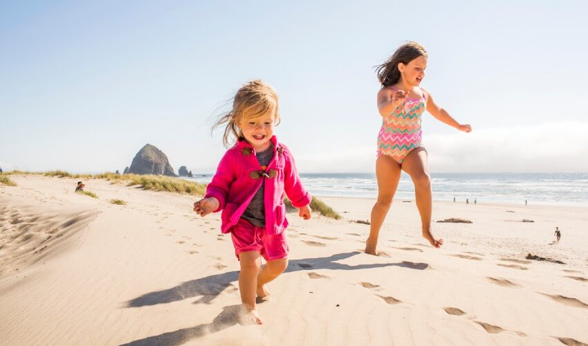 Two smiling small girls running on a sandy beach.